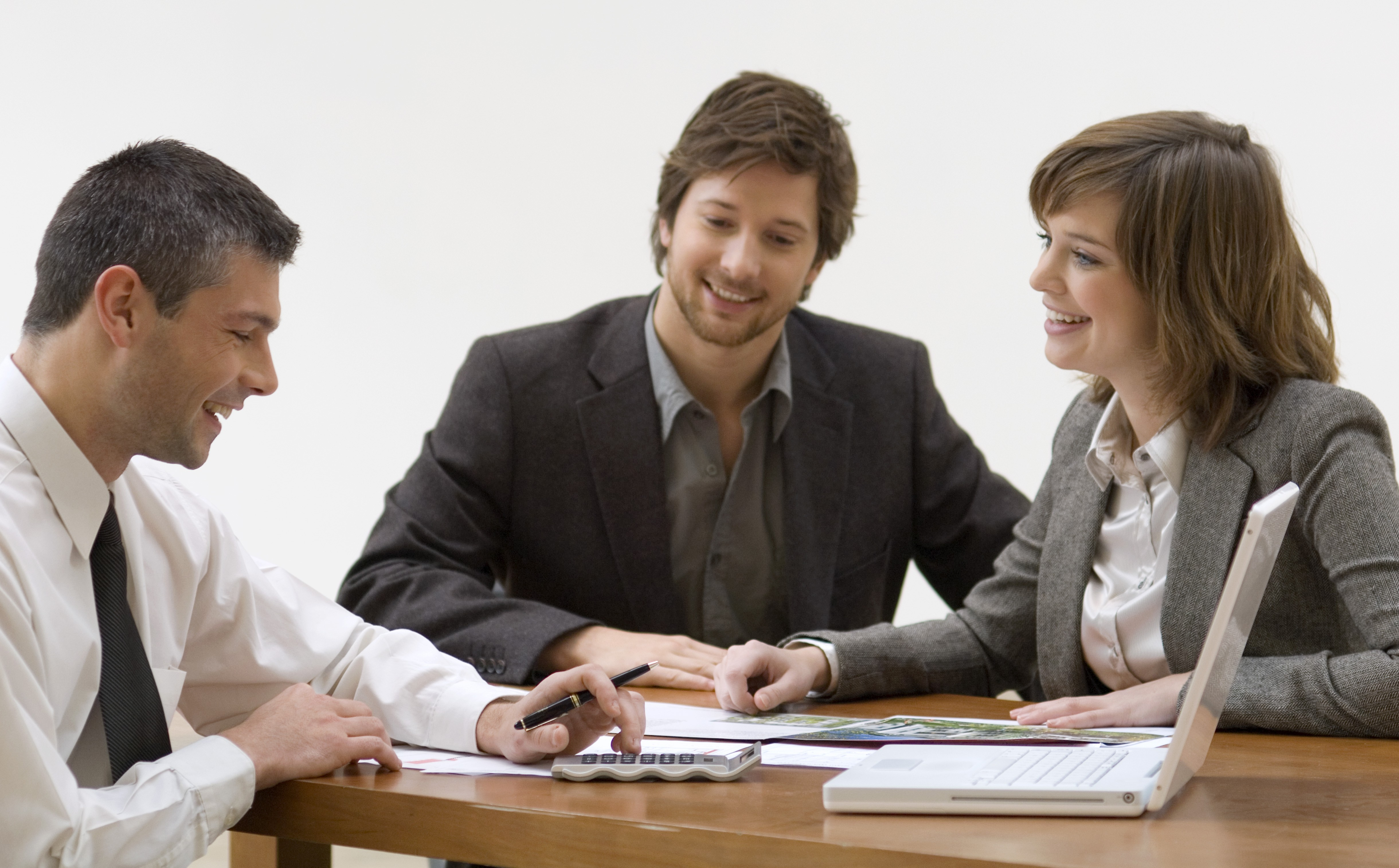Real estate agent discussing with a mid adult man and a young woman